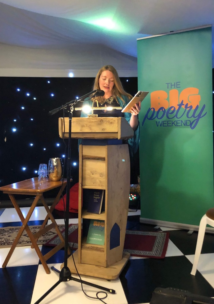 Zoe Brigley at a podium giving out the prizes for the Battered Moons Poetry Competition